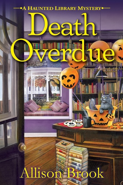 Book Cover. Death Overdue - A Haunted Library Mystery by Allison Brook. Jack-o-lantern balloons, skull cookies, and a gray cat inside a library.