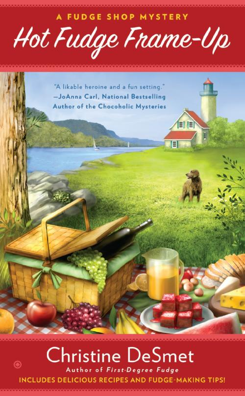 Book Cover. Hot Fudge Frame-Up - A Fudge Shop Mystery by Christine DeSmet. Picnic spread with pink fudge and lighthouse and dog in the background.