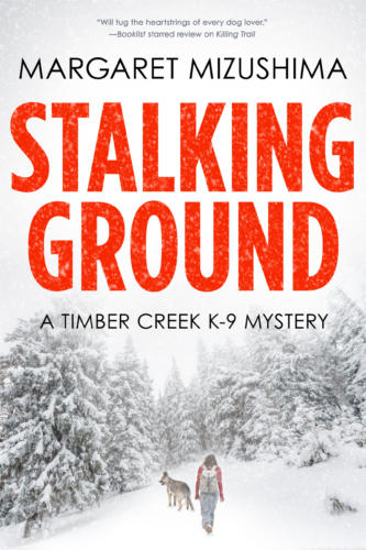 Book Cover. Stalking Ground by Margaret Mizushima. A Timber Creek K-9 Mystery. Person and dog walking in a snowy forest.