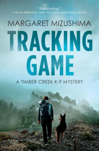 Book Cover. Tracking Game by Margaret Mizushima. A Timber Creek K-9 Mystery. A dog and a person walking on a mountain.